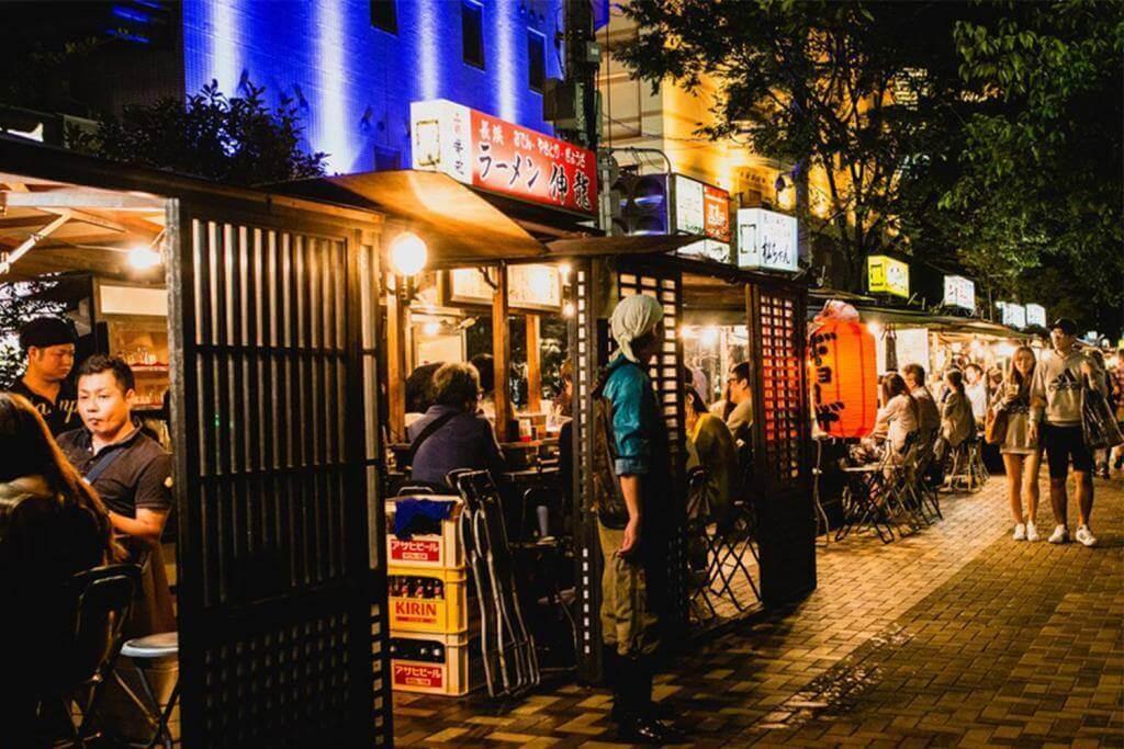 People eating Yatai mobile food stall at night in Fukuoka, Kyushu, Japan = Shutterstock