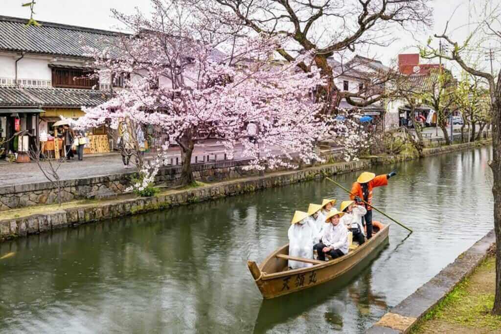 Unknown tourists are enjoying the old-fashioned boat along the Kurashiki canal in Bikan district of Kurashiki city, Japan = Shutterstock