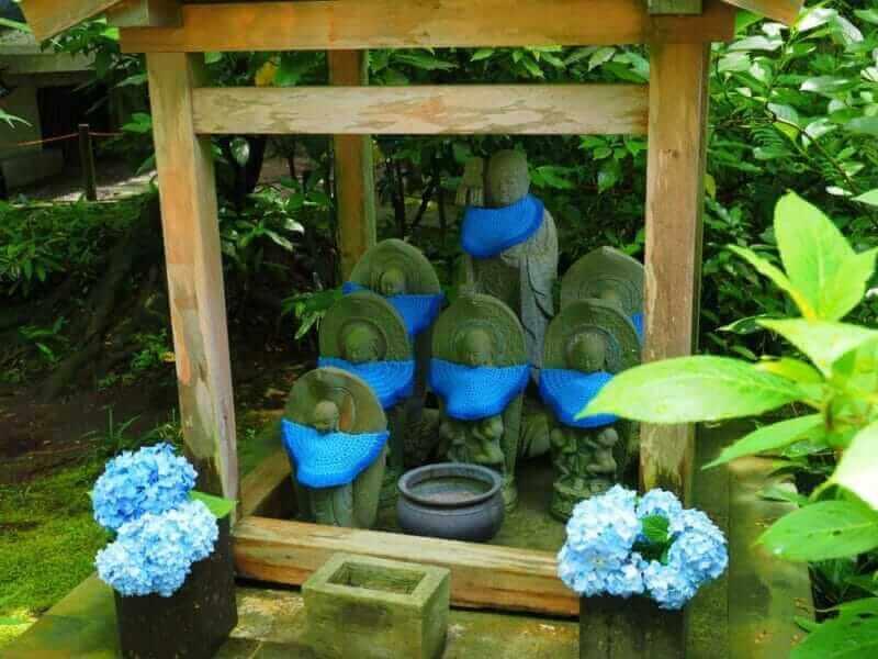 JIzo with blue bib in Meigetsuin temple Kanagawa,Japan = shutterstock