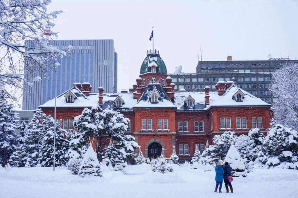 Gezicht op het voormalige regeringskantoor van Hokkaido in Sapporo, Hokkaido, Japan. Reiziger maakt in de winter een foto bij het voormalige regeringskantoor van Hokkaido in Sapporo, Hokkaido, Japan = Shutterstock