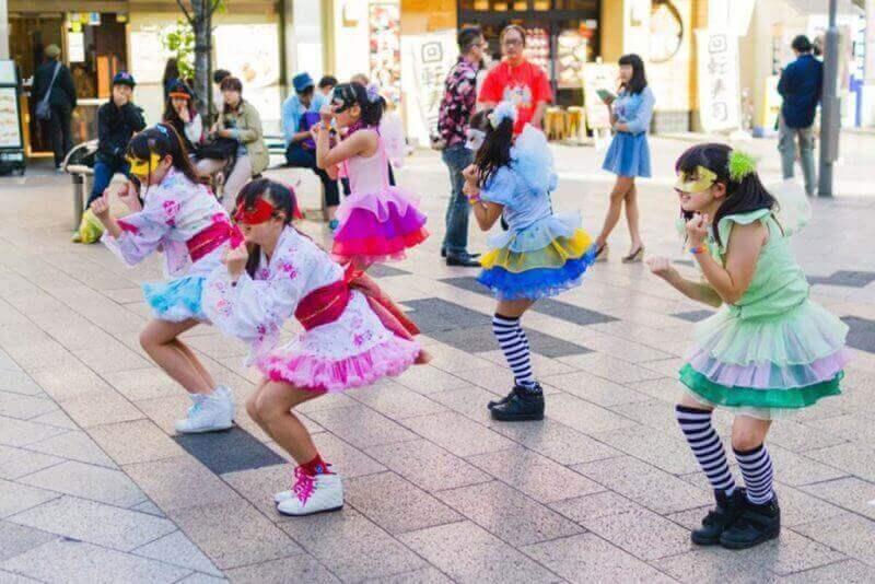 Молодая японская женская группа выполняет упражнение возле станции Акихабара в Токио
