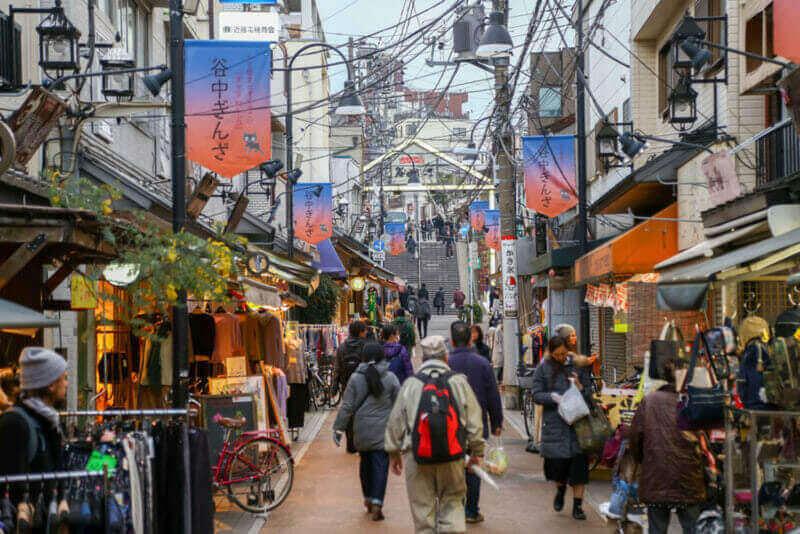 Люди, идущие на рынок Янесен в древнем торговом районе Японии - Вечерний свет = Shutterstock