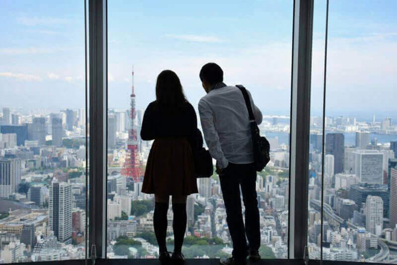 Любительница супружеской пары в Токио с видами на Токийскую башню с крыши башни Роппонги, Токио = Shutterstock